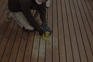 Horizontal photo of mature man kneeling while sanding outdoor wooden deck